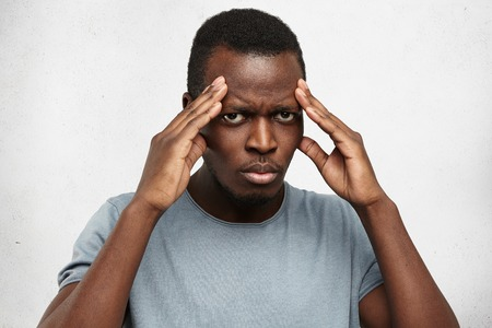 Serious young Afro-American man keeping hands on head, squeezing temples, having bad headache, looking at camera with painful expression. Dark-skinned male trying to concentrate on important issue