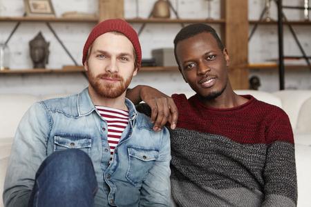 Glückliche Homosexuellen zwischen verschiedenen Rassen Paare, die drinnen Ruhe. African American männliche Ellbogen auf der Schulter seiner gut aussehenden stilvollen Partner in modischer Kleidung ruht, die beide in der Kamera mit freudigen Lächeln betrachten Standard-Bild