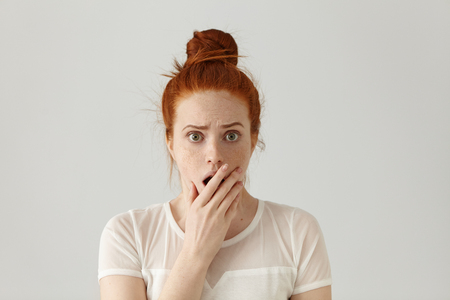 disbelief: Portrait of surprised amazed attractive young redhead female wearing white top having astonished face expression, covering her open mouth with hand, looking at camera in shock and full disbelief Stock Photo