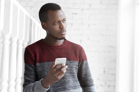 Mensen, technologie en communicatie concept. Binnenschot van nadenkende jonge Afrikaanse schrijver, die nota's in zijn mobiele telefoon maken terwijl wordt geïnspireerd met verbazend uitzicht in openlucht, kijkend door venster