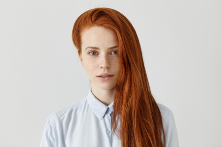 Gorgeous redhead student girl with long loose hairstyle wearing light-blue formal shirt getting ready for exams at college. Beautiful ginger young female of European appearance posing indoors