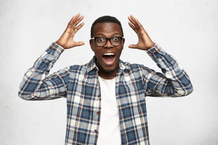 I cant believe this. Amazed young African American hipster wearing trendy glasses and checkered shirt over white t-shirt holding hands in surprised gesture, keeping mouth wide open, looking shocked