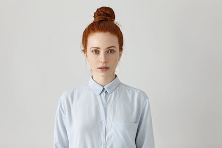 Indoor shot of attractive redhead young female office worker with hair bun posing at studio wall with copy space for your promotional content. Pretty girl dressed in formal shirt having rest indoors Фото со стока