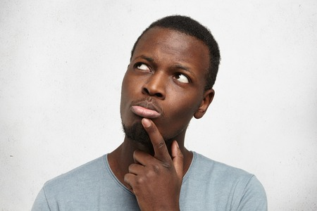 Human face expressions, emotions and feelings. Handsome young African American man looking up with thoughtful and skeptical expression, holding finger on his chin, trying to remember something Stock Photo