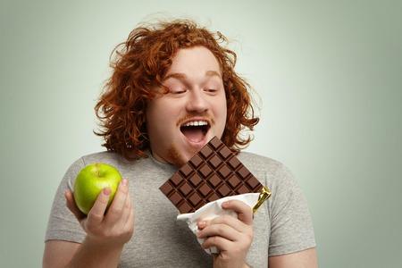 Hombre obeso del pelirrojo americano alegre que abre la boca extensamente, sosteniendo la barra de chocolate grande en una mano y manzana verde en otra, el elegir la comida basura apetitosa pero malsana sobre orgánica sana