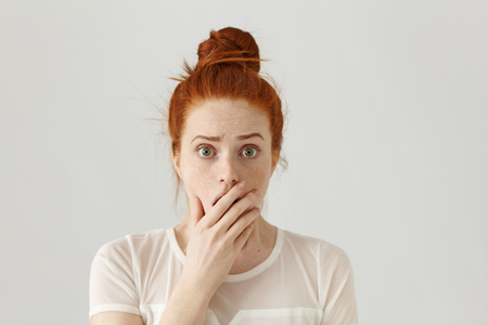 Scared and shocked bug-eyed pretty girl with orange hair having surprised and astonished facial expression while receiving shocking unexpected news, covering mouth with hand. Body language concept