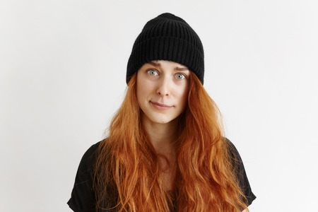 Indoor studio shot of cute redhead hipster girl wearing t-shirt and hat having indignant and blaming look, frowning and grimacing, pursuing her lips, doesnt approve something. Body language