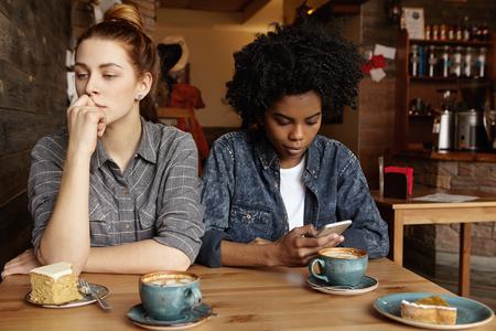 Las relaciones homosexuales y las tecnologías modernas. chica pelirroja hermosa que tiene mirada de preocupación, sentado en el café durante el almuerzo con su novia adicta a Internet africano, que obsesionado con el teléfono celular Foto de archivo