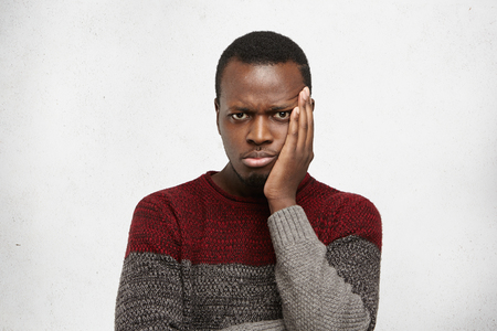 Indoor shot of unhappy young African man wearing warm sweater, touching his cheek while suffering from bad toothache, looking at camera with painful expression, waiting his turn at dentists