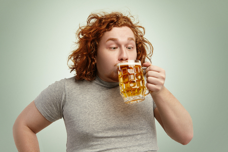 Close up shot of funny fat redhead make drinking cold lager out of glass, looking ridiculous. Obese overweight Caucasian man in casual t-shirt enjoying beer, standing against blank wall background Stock Photo
