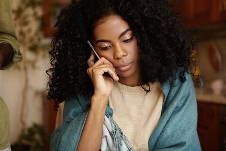 アフロ髪型は心配と不満を持っていると深刻な若い浅黒い女性が携帯電話で話している、悪い否定的なニュースを受けて、ラップを着て台所のテー