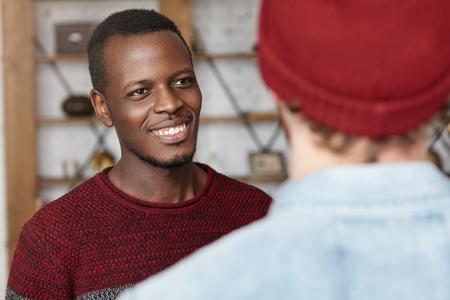 Les gens et le concept international de l'amitié. Heureux jeune homme à la peau sombre souriant joyeusement, en regardant son ami élégant méconnaissable qui il est tombé sur au restaurant pendant la pause déjeuner Banque d'images - 74225846