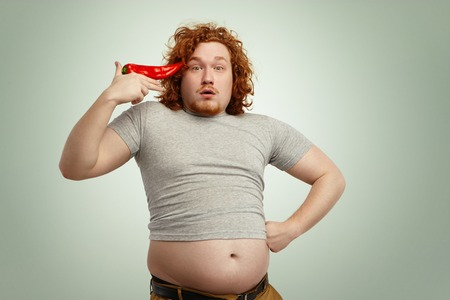 belly pepper: Funny overweight fat man with curly ginger hair holding big chile pepper at his temple like pistol, ready to shoot himself, having surprised expression with his belly hanging out of his grey t-shirt Stock Photo