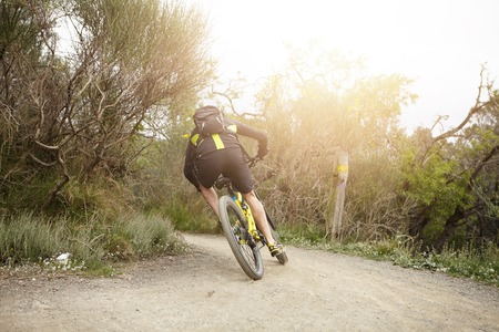 Back view of Caucasian biker wearing cycling clothes and backpack speeding on his MTB bicycle along trail in forest on Sunday morning, feeling extreme and adrenaline. Sports and active lifestyle Stock Photo