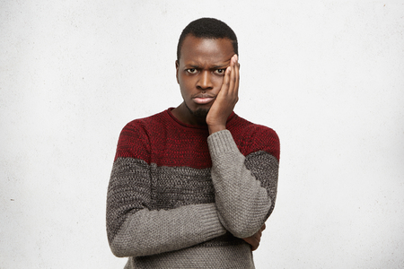 Headshot of unhappy frustrated young black male having puzzled expression, holding hand on his cheek and keeping arms folded. Sad African American man dressed in sweater feeling bored or depressed Stock Photo