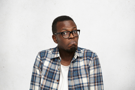 shot: I have no idea. Portrait of confused young African American male in glasses shrugging shoulders having hesitant and doubtful look, screwing up his lips. Human facial expressions and emotions