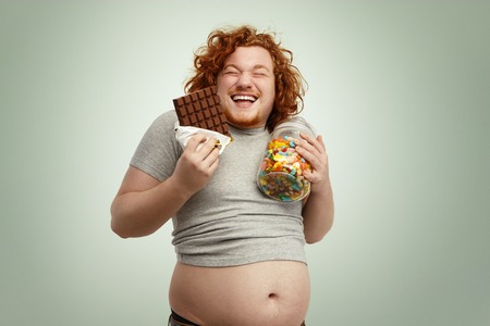 Indoor shot of fat redhead male holding glass of sweets in one hand and bar of chocolate in other, laughing, having sly look, anticipating eating sweets, his belly sticking out of undersized t-shirt Banco de Imagens
