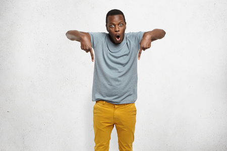 Check this out! Cropped studio shot of attractive excited young African male in t-shirt and mustard pants pointing fingers down having surprised look, his face expressing complete shock and disbelief