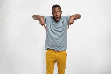 Bekijk dit! Bijgesneden studio shot van aantrekkelijke opgewonden jonge Afrikaanse man in t-shirt en mosterd broek wijzende vingers naar beneden hebben verbaasd blik, zijn gezicht uiten volledige schok en ongeloof