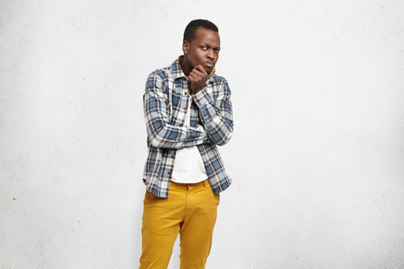 Portrait of stylish young Afro-American man dressed in mustard jeans and checkered shirt over white t-shirt having suspicious doubtful look, holding hand on his chin, thinking over something important Stock Photo