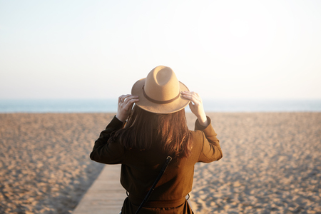 Back view of unrecognizable young brunette woman dressed in overclothes adjusting her stylish hat while spending nice time outdoors, walking along boardwalk down coastline to watch how sun goes down