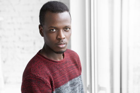 Portrait of handsome young dark-skinned male designer dressed casually having confident facial expression, relaxing indoors, standing by white window, contemplating urban view outside glass Stock Photo