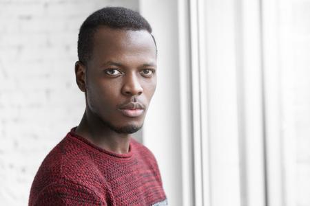 실내 포즈 심각한 모습으로 카메라를 응시하는 따뜻한 풀어머니 스웨터를 입고 젊은 아프리카 계 미국인 남자의 얼굴 만 귀하의 정보 내용에 대 한 복 스톡 콘텐츠