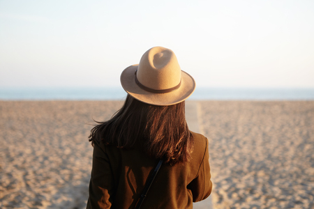 Rear view of young female with loose hair dressed in stylish warm clothing walking down coastline along boardwalk, spending holidays by ocean. Unrecognizable girl enjoying evening on city beach