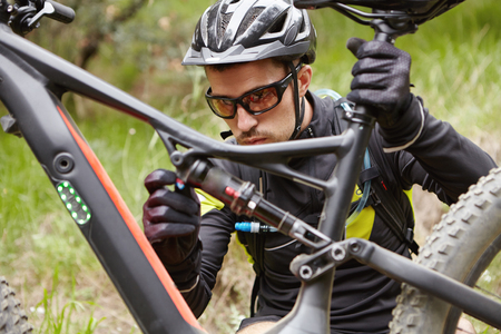 Close up shot of concentrated young rider in helmet, glasses and gloves sitting in front of his booster bicycle, checking its parts before cycling workout outdoors in forest. Cyclist repairing e-bike