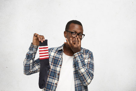 Fastidious young African American man wearing glasses and shirt over white t-shirt holding sweaty dirty stinky sock in his hand and pinching nose, his look expressing disgust with unpleasant smell