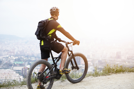 Sports, healthy lifestyle, inspiration and achievement concept. Rear view of young biker on mountain electric bicycle standing on top of hill and contemplating beautiful view of city down on sunny day