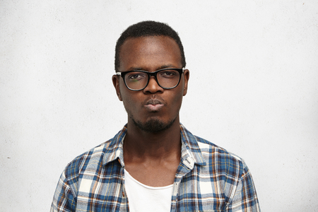 Young dark-skinned worker looking angry and offended, passive-aggressive and strongly unsatisfied, pursing his mouth with sadness and disappointment after conflict with his boss. Human emotions Stock Photo