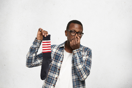 African American hipster dressed in glasses and checkered shirt over white t-shirt pinching nose because of bad smell of dirty stinky sock in his hand, looking at camera with disgusted expression Reklamní fotografie