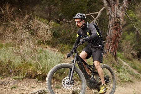 Handosme confident male cyclist in protective gear riding black electric motor-powered bicycle with pedal-assist system, cycling on trail in woods, overcoming obstacles and performing biking stunts Stock Photo