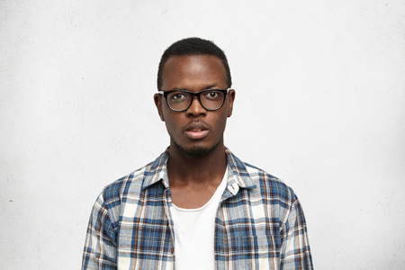 Young African American man student in big stylish eyeglasses standing isolated on white background and looking at camera with puzzled face expression, trying to figure complicated situation out