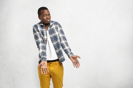 indignant: Indignant confused African American male in checkered shirt and mustard pants shrugging shoulders, stretching arms forward, staring at camera with questionable and clueless look, saying I dont know Stock Photo