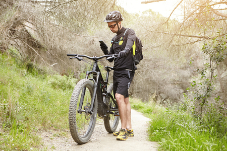 Outdoor shot of Caucasian male rider standing on trail in forest with his electric bike holding smart phone, checking GPS coordinates using map. Biker in glasses and helmet typing sms om mobile Stock Photo