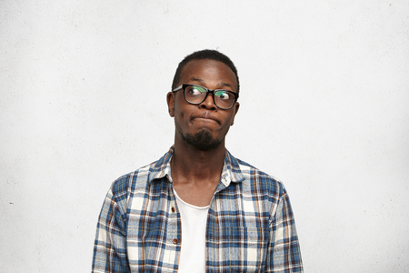 I dont know. Clueless funny young dark-skinned male wearing stylish glasses pursuing lips and looking sideways with doubtful and uncertain expression, feeling indecisive about his future plans Stock Photo