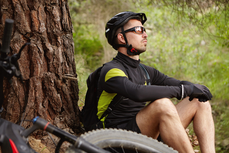 People, sports, nature and leisure concept. Relaxed carefree Caucasian biker in cycling clothing and protective equipment having small break during morning training, with his e-bike lying near him Stock Photo - 75993140
