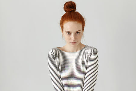 Indoor shot of cute redhead girl with hair knot wearing casual striped long-sleeved t-shirt, her posture expressing shyness. Beautiful young woman posing at blank wall with copy space for your text Stock Photo