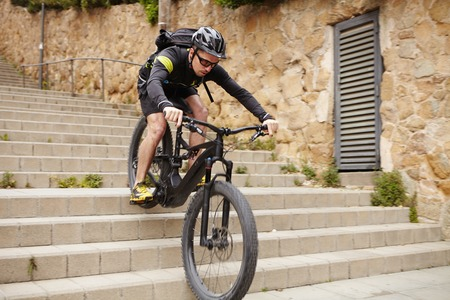 Young freerider in cycling clothing and protective gear performing bicycle tricks on electric two-wheeled vehicle in urban area, riding down concrete stairs. Sports, extreme and active lifestyle