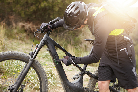 Unrecognizable Caucasian biker in helmet and gloves pressing buttons on frame of his black electric bike. Cropped view of young rider switching speed mode on control panel before cycling in forest
