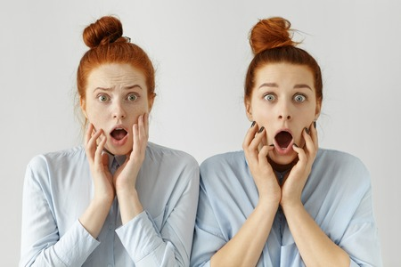 exclaiming: Portrait of scared clueless redhead female office workers wearing same knot hairstyles and formal shirts exclaiming, looking at camera with frightened expression, shocked and terrified with deadline Stock Photo