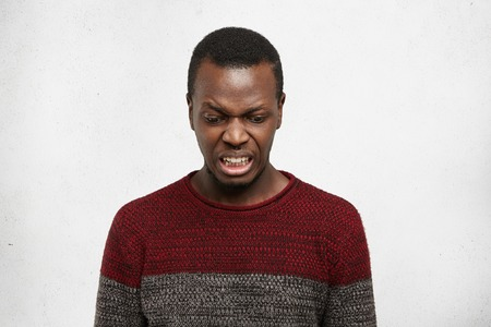 Angry fastidious young dark-skinned male wearing jersey sweater looking down, having squeamish scornful gaze posing indoors against gray wall background with copy space for your advertising content Stock Photo