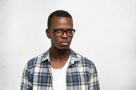 Studio shot of suspicious young African American hipster wearing stylish glasses frowning, looking at camera with distrust. Young black male model posing with serious look against white background