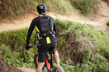 Back view of cyclist in black clothes riding electric bycicle in rural hilly area, ideal for freeride. Young Caucasian biker exercising on his booster motor-powered bike, preparing for cycling contest