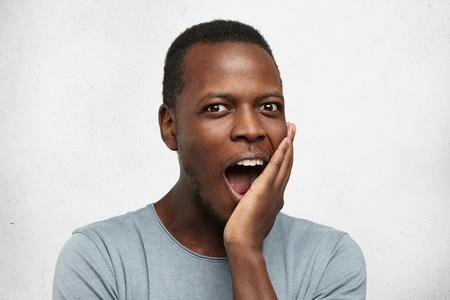 幸せな興奮若いアフリカ系アメリカ人男に驚き、灰色 t シャツ オープン口の中で彼の顔に触れると魅了な式で彼の心を交差させた素晴らしいアイデ