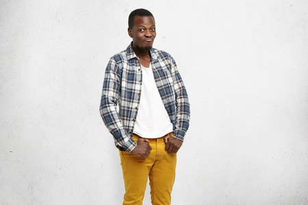 Confused frustrated dark-skinned male wearing mustard pants and checkered shirt over white t-shirt, pursuing lips and raising brows, his look and posture expressing indifference and disinterest