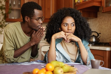 Afro-American couple going through hard times in their relationships. Guilty unfaithful young man keeping hands pressed begging his angry wife to forgive him for infidelity, trying to sweet talk her
