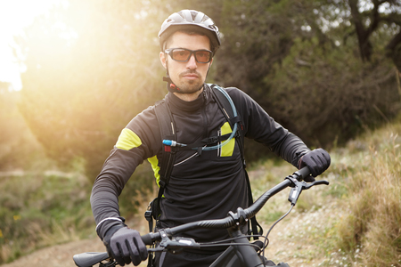 People, sports, fitness and active healthy lifestyle concept. Attractive biker in protective gear looking at camera, having rest while riding his battery-powered bicycle in forest on sunny spring day Stock Photo